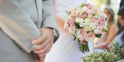 groom and bride with bouquet at outdoor summer wedding