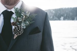 groom with winter wedding decor